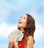 sale, banking and people concept - smiling woman in red dress with us dollar money over blue cloudy
