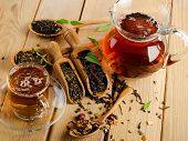 stock photo of black tea  - Cup of tea and assortment of dry tea in spoon on a wooden background - JPG