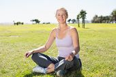 Fit mature woman sitting in lotus pose on the grass on a sunny day