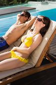 Side view of a young couple resting on sun loungers by swimming pool