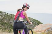Rear view portrait of an athletic young woman mountain biking