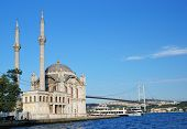 ISTANBUL, TURKEY - AUGUST 7, 2007: Fishermen under the Ortakoy mosque against the Bosporus bridge. T