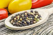 Various peppercorn mix on a vegetables background