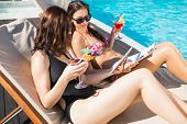 Two beautiful young women holding drinks by swimming pool