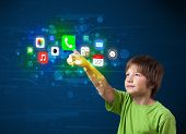 Young boy pressing colorful mobile app icons with bokeh background