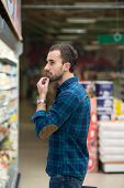 picture of department store  - Handsome Young Man Shopping For Fruits And Vegetables In Produce Department Of A Grocery Store - Supermarket - Shallow Deep Of Field