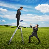displeased man standing on stairs and looking down at businessman in fighting stance. outdoor photo