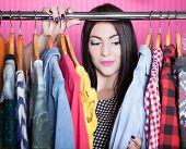 Time to refresh wardrobe young attractive surprised woman searching for clothing in a closet