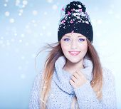 Winter face close up of young attractive woman wearing hat covered with snow flakes. Christmas concept.