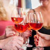 image of shot glasses  - Macro Shot of Hands Raising Glasses of Tasty Red Wine in a Social Gathering - JPG