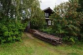 Old Wooden Country House With Stack Of Boards