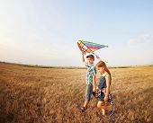 picture of kites  - Happy boy and little girl with bright kite on a meadow in a sunny evening - JPG