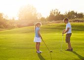 Kids At A Golf Field Holding Golf Clubs. Sunset