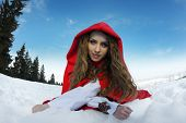 beautiful woman with red cloak sitting on the snow