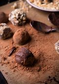 pic of truffle  - Assorted dark chocolate truffles with cocoa powder biscuit and chopped hazelnuts over baking paper selective focus - JPG