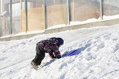 picture of snowy hill  - Child climbing on a snowy hill in winter - JPG