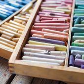 Set Of Multicolored Pastel Crayons In Open Wooden Artist Box On Rustic Desk. Selective Focus.