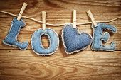 The Love word made of jeans letters with a jeans heart on a rope on a vintage wooden background. St. Valentine's day concept.