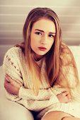 Beautiful sad, worried caucasian woman in bright sweater.