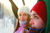 portrait of two beautiful sporty girls with snowboards