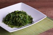 Seaweed salad in plate on bamboo mat and wooden table background