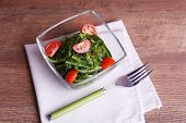 Seaweed salad with slices of cherry tomato in glass bowl on napkin and wooden table background