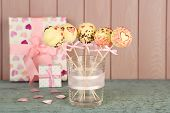 Tasty cake pops and gifts on wooden background