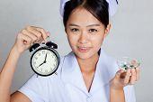 Close Up Asian Young Nurse With Clock And Pills