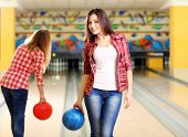 stock photo of bowling ball  - Young women holding bowling ball in club - JPG