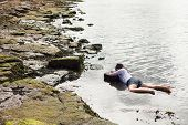 stock photo of accident victim  - View of a young woman washed up on rocks at the edge of a river - JPG