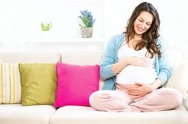 picture of maternity  - Pregnant Happy smiling Woman sitting on a sofa and caressing her belly - JPG