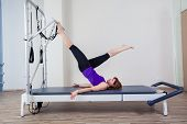 picture of stretch  - gym woman pilate instructor stretching in reformer bed - JPG