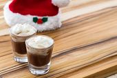 picture of peppermint  - holiday shooters chocolate and peppermint on a wooden background with a red santa hat - JPG