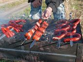 picture of grilled sausage  - Man cooking sausages on the grill outside - JPG