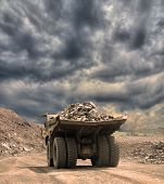 foto of dump_truck  - Heavy dump truck with iron ore on the opencast on stormy sunset - JPG
