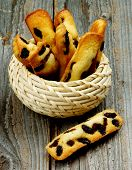 picture of baked raisin cookies  - Tasty Biscuit Raisin Cookies in Wicker Bowl closeup on Rustic Wooden background - JPG