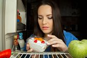 picture of refrigerator  - sad hungry woman with dessert inside refrigerator - JPG