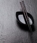 image of soy sauce  - Japanese sushi chopsticks over soy sauce bowl on black stone background - JPG