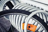 picture of fragmentation  - Fragment of a parked bicycle wheel with bright orange reflector vintage toned photo - JPG