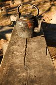 foto of kettles  - Old kettle in wooden bench outdoors in sunlight - JPG