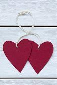 picture of two hearts  - Vertical Image With Two Empty Red Hearts Label With White Ribbon On White Wooden Background - JPG