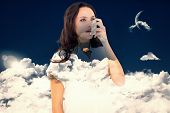 stock photo of inhalant  - Asthmatic brunette using her inhaler against night sky - JPG