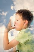 picture of asthma  - Boy using asthma inhaler in hospital against bright blue sky with clouds - JPG