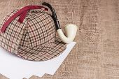 stock photo of private investigator  - Deerstalker or Sherlock Hat and Tobacco pipe on Old Wooden table - JPG