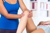 picture of physiotherapy  - young woman lying while getting a leg massage from specialist concept of physiotherapy - JPG