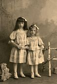 picture of old-fashioned  - A vintage photo of two little sisters are looking at camera with identical frocks hair bows and shoes - JPG