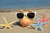 picture of piggy  - Summer piggy bank with sunglasses on the sand - JPG