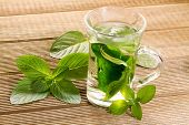 stock photo of mints  - Mint tea with fresh mint leaves on a wooden background - JPG