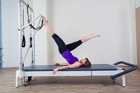 foto of pilates  - gym woman pilate instructor stretching in reformer bed - JPG