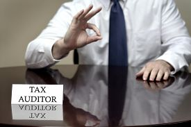 stock photo of irs  - IRS tax auditor business card sitting at desk with hand showing OK sign for audit success - JPG